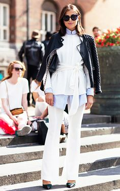 A blue button-down shirt is paired with a belted white blouse, leather jacket, white flare pants, and pumps