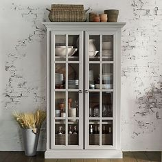 Statuesque wood cabinet shows its lighter side with a warm grey finish and pane glass fronts to showcase dinnerware, books or bed linens. Classic yet clean styling includes crown and base molding and ring pulls.