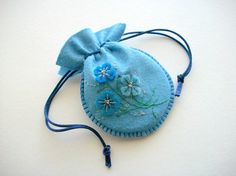 Blue Gift Bag Felt Jewelry Pouch with Hand Embroidered Felt Flowers Handsewn $17.00 The pouch is pulled by strong blue satin cords and is plain on the back. The bag is 9 x 12 cm or about 3.5 x 4.7 inches measured at the widest points. It has no lining.