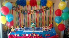 Sesame street themed dessert table.  Desserts included; cookie monster chocolate lollipops, chocolate and vanilla cupcakes, #1 and Elmo shaped cookies and birthday cake.  Table was custom decorated to fit theme and all characters and banners were custom cut - www.dolcerellabakery.ca
