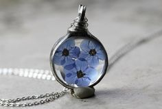 Blue forget me nots between soldered glass. It hangs from your choice of silver plate or sterling silver chain finished with wire wrapped stones.