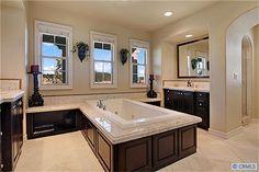 Master bath with dual vanities across marble flooring