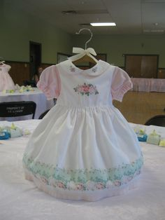 Smocked baby dresses for a  baby girl shower center piece. The dresses are held up with an infant hanger wired to a doll stand. I also stuffed the inside with tissue paper to add fullness to the dress.