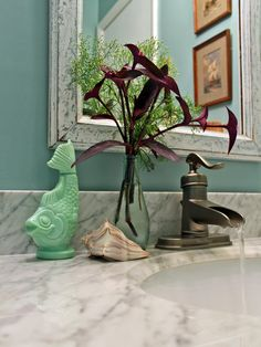 Choose coastal-inspired accessories, like this jadeite fish-shaped bottle and a found shell,  when decorating a beach house bathroom.