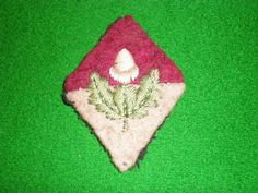 Embroidered diamond featuring the Cheshire Regimental colours of maroon and buff superimposed with the Regiment's acorn badge. This badge has been associated with the Heswall Battalion of the Cheshire Home Guard and was possibly worn before the introduction of the standard HG numerals and letters.