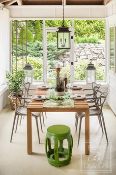 The dining area. Kingsley Bate teak table and Starck chairs. Darby Road Antiques antique wood leg candlestick holders, custom runner and terrarium adorn the table. Designer: Barbara Elza Hirsch of Elza B. Design. Photo Credit: Irvin Serrano
