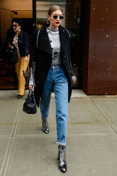 Street style Queen Gigi Hadid worked high waisted jeans, gold-rimmed sunnies, and metallic Stuart Weitzman boots while out in NYC.