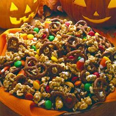 Trick or Treat Caramel Corn 16 cups plain popped popcorn 5 cups miniature pretzels 2 cups firmly packed brown sugar 1 cup Land O Lakes® Butter 1/2 cup dark corn syrup 1/2 teaspoon salt 1/2 teaspoon baking soda 1 cup salted peanuts 1 cup candy-coated milk chocolate pieces 1 cup candy corn