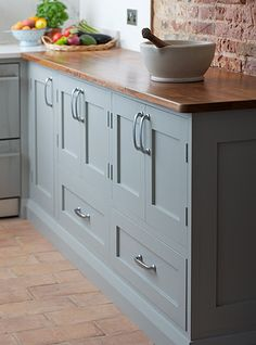 love the combination of wooden counter with painted cabinets