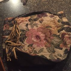 Floral purse Cream floral print bag with one faux leather handle and tassel. Super cute and roomy! Has one zipper compartment. Good condition!  Claire's Bags
