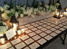 Vintage planter boxes and blooms and a reclaimed wood table make the perfect escort card table