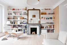 Living room with floor to ceiling bookshelves, a fireplace, and a white sofa
