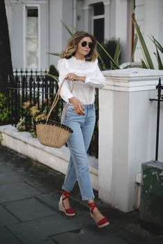 Emma Hill wears broderie anglais blouse, bleach wash Paige jeans, straw basket bag with pom pom detail, red canvas espadrilles, Ray Ban round metal sunglasses in gold, spring summer outfit
