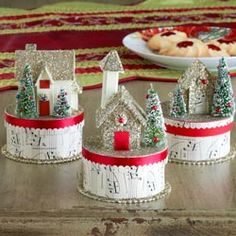 Paper houses adorn boxes covered in sheet music - would make adorable table scape treats