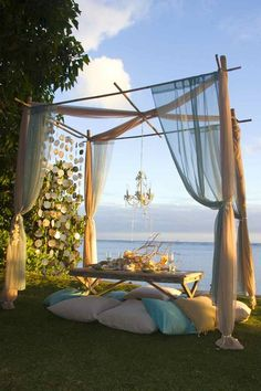 beach wedding, canopy over romantic dinner table with pillow seating