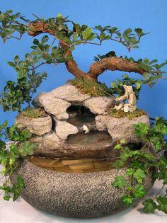 """Pequeño tazón de fuente del loto Color: Tazón de fuente Textured de la piedra gris Tamaño: los 13in. Diámetro Aprox. Altura: 11 """"a 13"""" desde la parte inferior del tazón hasta la parte superior del árbol) Esta pantalla de fuente de agua incluye un pescador y un árbol de Bonsai artificial. Plantas vivas pueden ser sustituidas si lo desea. Será entregado a su puerta"""