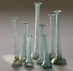 Ancient Roman blown glass perfume containers in excellent condition. Many were colored light green or blue and came in a variety of shapes and sizes. 2nd-4th century AD.