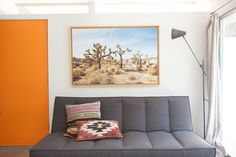 Living room, dark sofa, orange door, picture  //Design Inspiration From a Palm Springs Desert Chic Boutique Hotel, The Amado
