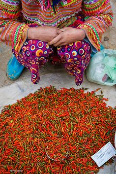 Chili peppers sold by someone even more colourful - Bac Ha market, Vietnam