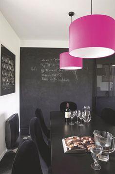 L'un des murs a été recouvert d'une peinture noire sur laquelle les enfants peuvent écrire à la craie. Table en bois noir, Mise en demeure, chaises noires, Tolix et AM.PM., et suspensions noires et fuchsia, Habitat.