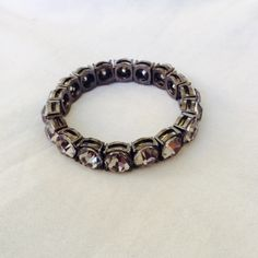 LOFT gunmetal and gray rhinestone bracelet Grey and silver rhinestone bracelet from ANN TAYLOR LOFT elastic and stretchy. Never worn, round large stones. LOFT Jewelry Bracelets