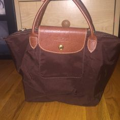 Longchamp 'Mini' Le Pliage Handbag Longchamp Le Pliage 'Mini' Tote. In excellent condition since I've only used it two or three times. Has some surface air bubbles from being stored away for so long but has ABSOLUTELY NO STAINS OR DISCOLORATION! Message me if you need more info! Longchamp Bags Mini Bags