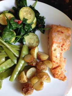 Salmon cooked in garlic chilli sauce with spinach, courgettes, mangetout and roasted baby potatoes