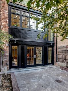 The rear facade of this Brooklyn townhouse is painted all-black, a bold decision that lends drama to the traditional structure. A bricked terrace adds to the home's livable space, while a tall fence provides privacy.