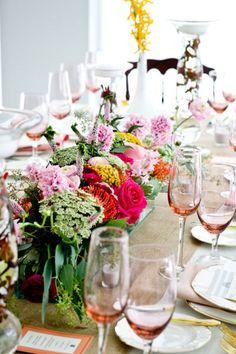 tablescape: blush-colored glasses, vibrant centerpiece, burlap runner, gold flatware.
