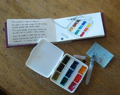 A small watercolor sketching paintbox- Looks like someone else discovered that this small first aid kit (3x4x1 inch) would make a good paintbox. She has 9 full pans pf paint here in hers. Mine is stuffed w/23 half pans of yummy artist quality watercolors! With a pen, water brush, and a sketchbook, etc...you're set to go!