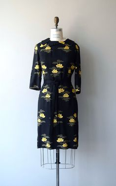 Vintage 1960s black cotton/linen blend sheath dress with yellow embroidered lilipads, 3/4 sleeves, princess seams, unbanded waist, self-fabric tie belt and back metal zipper. --- M E A S U R E M E N T S --- fits like: medium shoulder: 16 bust: 38 waist: up to 33, ties to fit waist hip: up to 40 length: 38 brand/maker: Syd | Chicago condition: excellent ✩ layaway is available for this item To ensure a good fit, please read the sizing guide: http://www.etsy.com/shop/DearGolden/policy ✩ mor...