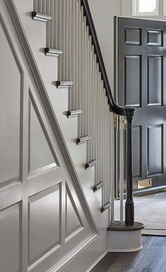 A staircase wall with gray wainscoting features a black handrail with white wood. A staircase wall with gray wainscoting features a black handrail with white wood spindles around dark oak floors and a black entry door. Dark Staircase, Black Stair Railing, Black Stairs, Staircase Design, Black Entry Doors, White Hallway, Wood Handrail, Banisters, Staircase Spindles