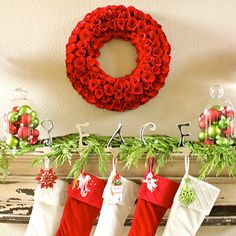Red and Green Christmas Mantel  A simple display in traditional red and green instantly adds Christmas spirit to a mantel. Color-coordinated ornaments sit in glass clouches and a mix of foliage with a floral wreath. Glittery ornaments hang on metallic P E A C E stocking holders.
