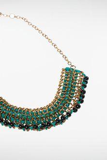Arborez ce collier plastron qui illumine votre allure et vous donne une véritable prestance ! Il rappelle les colliers ethniques avec ses perles multicolores entrelacées à une chaîne de métal doré. Le tout est monté sur des anneaux de métal. On ferme le collier par un fermoir mousqueton et une chaînette de réglage. Collier plastron, perles multicolores, anneaux de métal, chaînette de réglage, fermoir mousqueton.<br/>