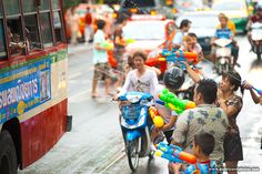 Innocent motorcyclists are caught in the crossfire of a watery battle with a bus during Songkran water festival.