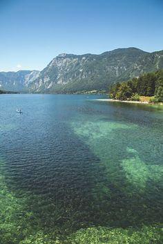 """Lake Bohinj shows off its vibrant colors in the summer sunlight. The lake is a popular destination for boating and kayaking. 
