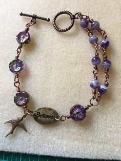 This bracelet is made with antique copper wire and purple glass beads. It has BELIEVE on the charm with a bird dangling.