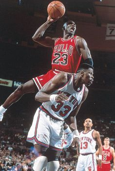 Jordan holds himself up on Ewing While He Shoots Over Him