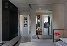 Contemporary Loft Finds The Perfect Balance Between Cool And Elegant The master bedroom suite has an interesting layout. The bathroom open into the actual room and the minimalist gray tub and the bed sit parallel to each other with just a piece of glass between them.