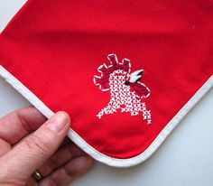 Vintage red napkins with white binding and cross-stitch embroidered rooster.