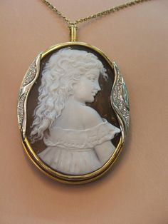 cameo of a child as a pendant with some sort of stones on edge