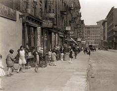 Depression era street life with children playing and dancing in the street. Lots of vintage storefronts and two 1920 cars parked. 28th street looking east from Second Avenue. New York. April 1931. by wavz13, via Flickr