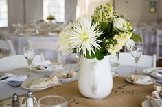 White pitchers filled with flowers centerpieces. Each white pitcher is different and hand picked from numerous antique shops and flea markets across New England.