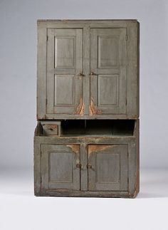 New England Painted Step-back Cupboard,  possibly Vermont, ca 1790-1820. A New England step-back cupboard made in two pieces with a dry sink base. Retaining an older, gray, painted surface over an earlier painted surface; ht. 90.5, wd. 52, dp. 24 in.