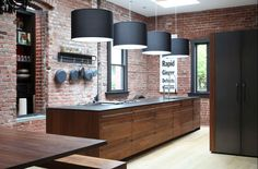 This Industrial-style kitchen features exposed brick walls, oversized drum pendant lighting, and a large kitchen island with black countertop and wooden drawer cabinetry. Design Loft, Küchen Design, Design Case, House Design, Interior Design, Design Ideas, Wall Design, Brick Design, Bar Interior