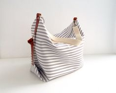 El bolso Messenger Marina es un bolso de tamaño grande, donde podrás llevar de todo. Confeccionado en loneta de rayas gris y blancas con detalles