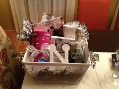 "Bride to be basket! I made this for my best friend Shawna . Her fiancé gave it to her the night of their engagement. Contents : bridal magazine, bottle of moscato champagne, ring pops, candle, picture frame that says ""bling bling I got the ring"", wedding wine glass, my clutch that I used for my wedding ( something borrowed)and a glittery initial of her soon to be new last name"