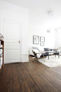 Dark wood flooring coupled with an all white living room, so stylish.