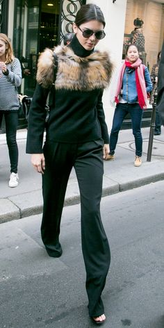 The model looked every bit the Parisian lady while leaving the Chanel offices in Paris, wearing a fur-trimmed Sally Lapointe sweater, black pants, black sandals, and sunnies. A loose chignon finished the show-stopping look.