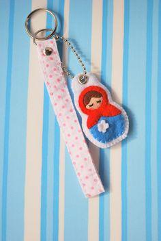 Matrioska em feltro vermelho e azul com tira de tecido com fundo branco e poás rosa. R$5,00